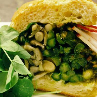 Sandwich with mushrooms, asparagus, pea tendrils, pistachios pesto, and radish at Dirty South Deli