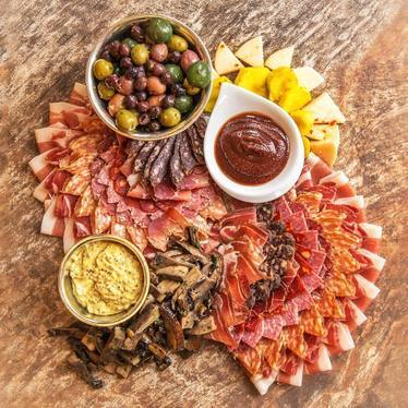 Charcuterie board with salami, olives, cheese, and mushrooms at Rainier Club