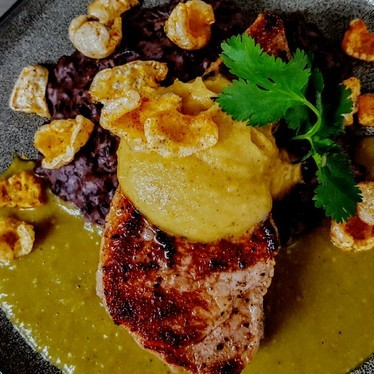 Island pork rib chop, chili verde, mango-browned butter, turtle bean mash and chicharones at Copper Bar