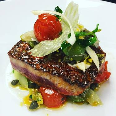Bluefin tuna, fennel pollen and lemon zest crust, roasted cherry tomatoes, charred palma, shaved celery at STK Downtown