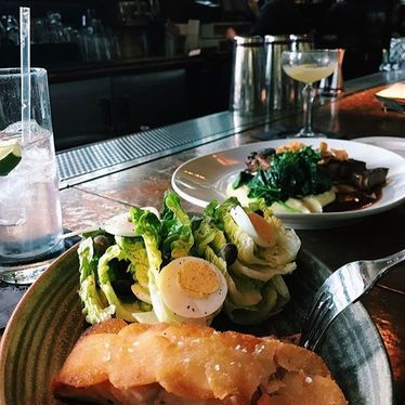 Potato crusted salmon, eggs on lettuce at Absinthe Brasserie & Bar