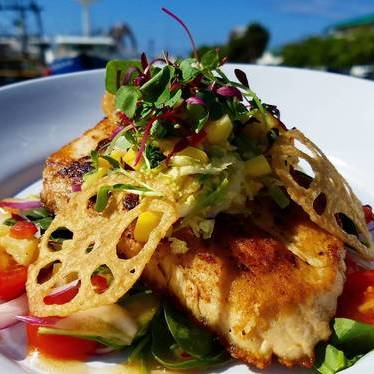 Opah with curry, pineapple-mango cabbage slaw, lotus roots, spinach, and plum vinaigrette at Nico's at Pier 38