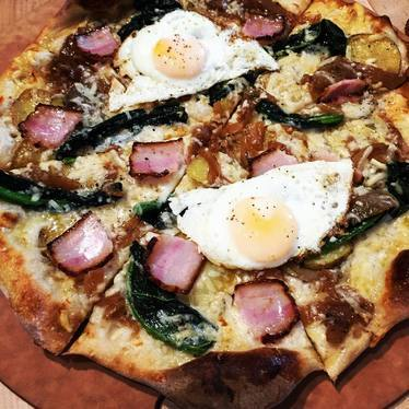 Pizza with potatoes, kale, caramelized onions, bacon, provolone and fried eggs at Southpaw