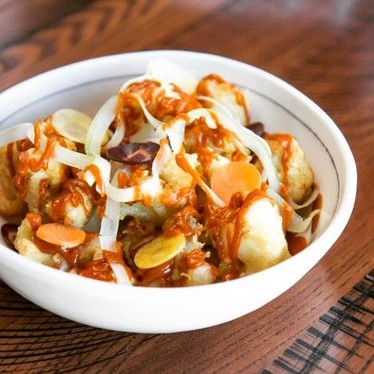 Tempura cauliflower with kimchi hot sauce, carrots and celery at Riel