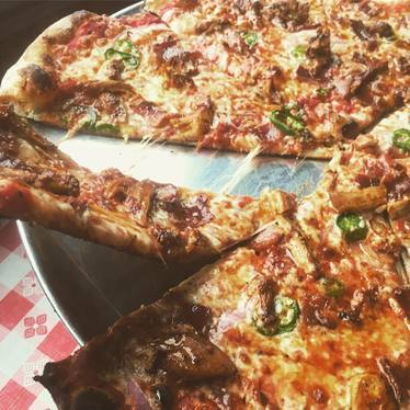 BBQ chicken pizza with wing sauce, bacon, red onion, honey and jalapeños at Pizza Jerk