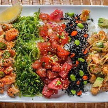 Poke Chirashi, with Original Ahi, Salmon Avocado and Spicy Serrano Poke, wakame salad, Hijiki salad, cucumber, daikon sprout salad on warm seasoned short-grain rice at Pacific Catch