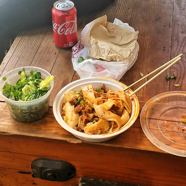 """Spicy pork noodles and herb salad """"al fresco"""" at Xi'an Famous Foods"""