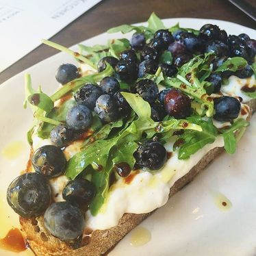 Toast with blueberries, greens, oil and vinegar at The Kitchen