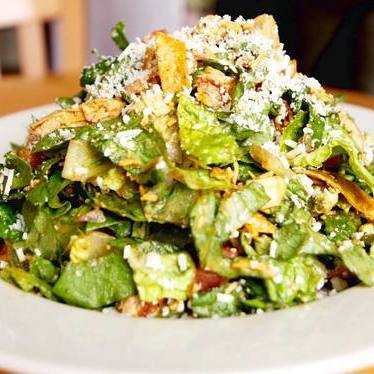 Salad with chicken, tomatoes, red onion, avocado, cheddar, tortilla strips, honey-lime vinaigrette, and cotija cheese at Mother's Bistro & Bar