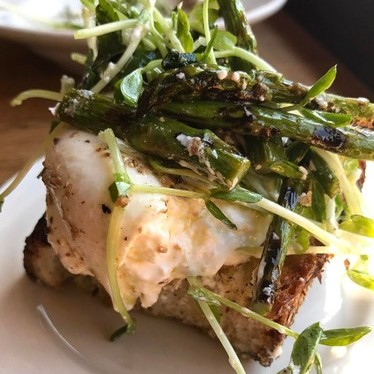 Burrata and black truffle vinaigrette, asparagus, pea shoots on Filone toast at Frankies Spuntino